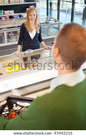 A woman flirting with a man in a grocery store - stock photo