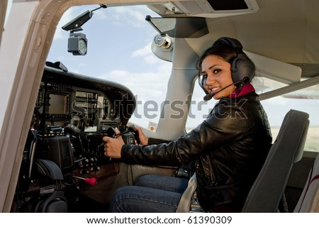 A woman flying an airplane - stock photo