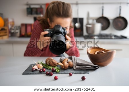 A woman food photographer in the background leans down to take a close-up, in a modern kitchen, of autumn fruits and vegetables - mushrooms, garlic, rosemary, and cranberries. - stock photo