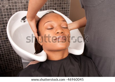 a woman gets her hair washed before getting a cut - stock photo