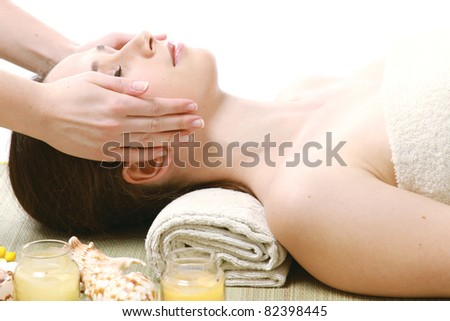 A woman getting a face massage, isolated on white - stock photo