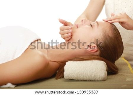 A woman getting a face massage, isolated on white background - stock photo