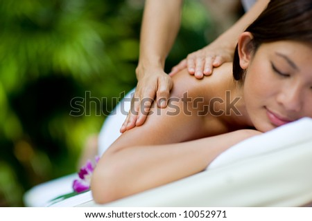 A woman getting a massage at a tropical spa - stock photo