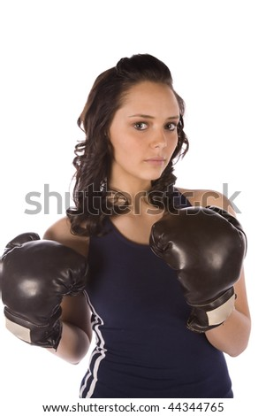 A woman getting exercise by boxing and getting in shape, with a serious look on her face.