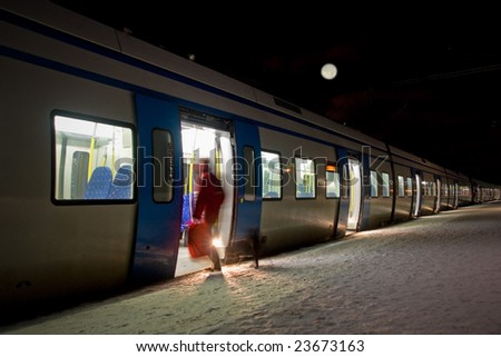 A woman getting on a train in the evening. - stock photo