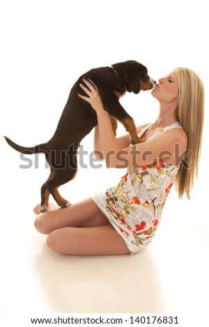 a woman getting ready to give her dog a kiss.