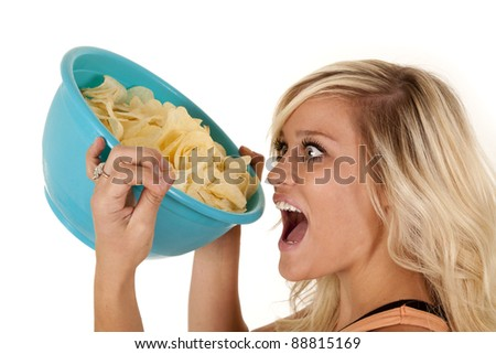 a woman getting ready to pour the whole bowl of chips into her mouth with a hungry expression on her face. - stock photo