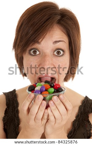 A woman getting ready to put a bowlful of jelly beans in her mouth.