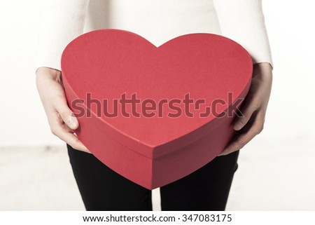 A woman(girl, female) wearing white sweater(shirts), black pants hand hold a red heart(love) gift box(package) isolated white at the studio.