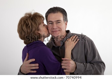 A woman gives her partner a little kiss on the cheek while he smiles appreciatively. - stock photo