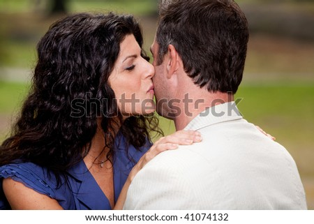 A woman giving a man a kiss on the cheek - stock photo