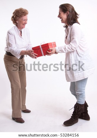 A woman giving a surprise gift to her mother - stock photo