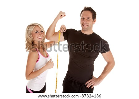 A woman giving her thumbs up at how big her man's muscles are. - stock photo