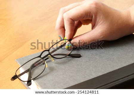A woman grabs her glasses to begin her reading experience. - stock photo