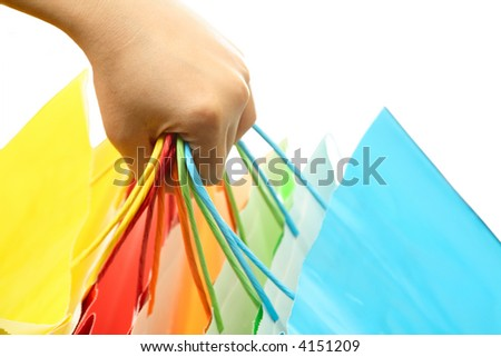 A woman hand carrying a bunch of colorful shopping bags - stock photo