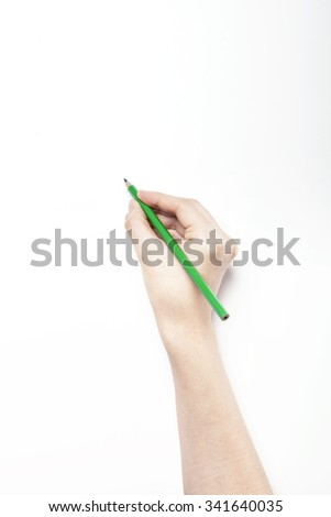 A woman hand hold a green pencil on the white desk(table, board) top view isolated white at the studio.