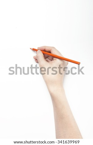 A woman hand hold a orange pencil on the white desk(table, board) top view isolated white at the studio.