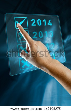A woman hand selects 2014 on a digital screen  - stock photo
