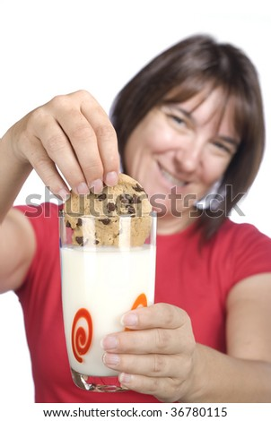 A woman happily dunks her chocolate chip cookie into a cold glass of milk.  Good image for snacking inferences for adult age groups and unhealthy eating concepts.