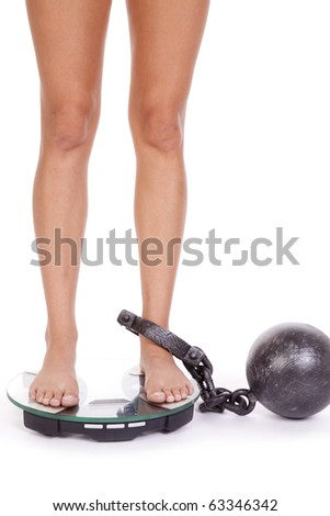 A woman has a ball and chain on her leg and standing on the scales. - stock photo