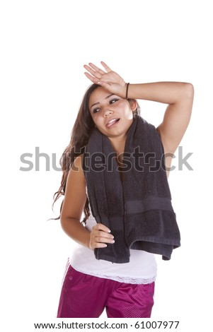A woman has a towel around her neck and looks exhausted from her workout. - stock photo