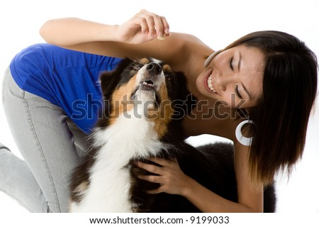 A woman has a treat for her dog on white background