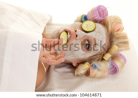 A woman has curlers in her hair and a cream face mask holding a cumber slice. - stock photo