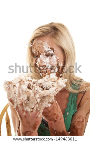 A woman has pie all over her face and is very messy - stock photo