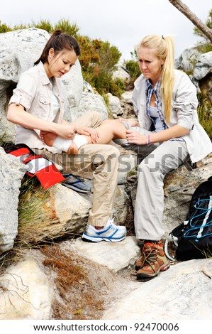 A woman has sprained her ankle while hiking, her friend uses the first aid kit to tend to the injury - stock photo