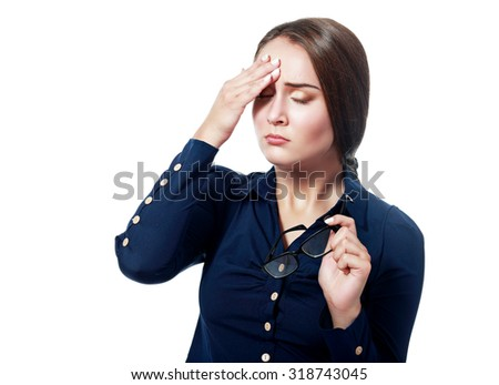 A woman having a headache, closeup over white hold glasses in her hand - stock photo