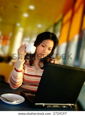 A woman having coffee while working on her laptop computer, at the airport lounge.