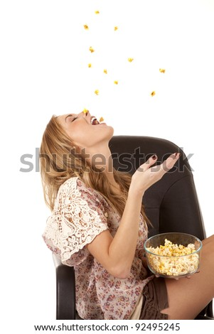 A woman having some fun by throwing a handful of popcorn into the air and trying to catch it in her mouth.