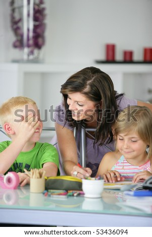 A woman helping a boy and a girl doing homework - stock photo