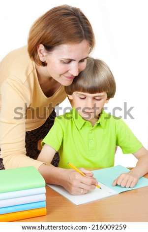 A woman helps first graders how to write in a notebook  - stock photo