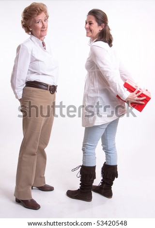 A woman hiding a surprise gift from her mother - stock photo