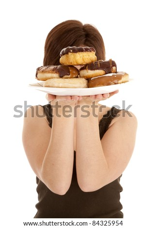 A woman hiding her face behind the big pile of doughnuts.