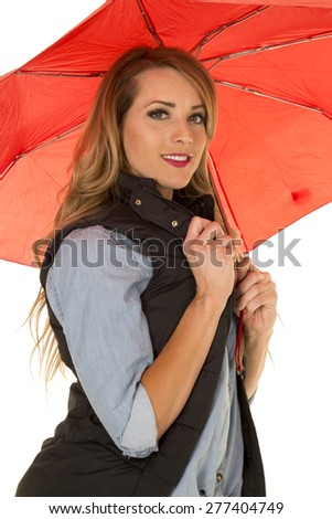 A woman hiding under her umbrella with a smile on her lips. - stock photo