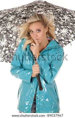 a woman hiding under her umbrella with the wind blowing her hair. - stock photo
