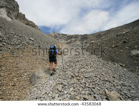 A woman hiking beside Mount Rae on the Ptarmigan Cirque Trail in Peter Lougheed Provincial Park, Alberta, Canada. - stock photo