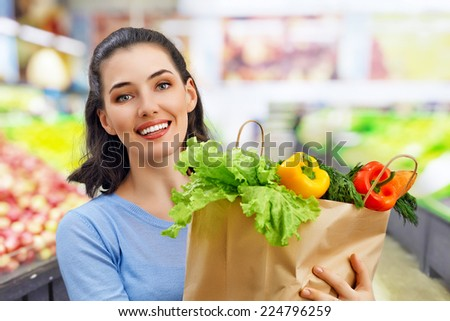 a woman holding a bag of fruit - stock photo