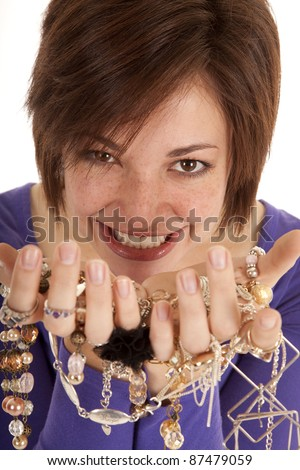 A woman holding a bunch of jewelry with a greedy expression on her face.