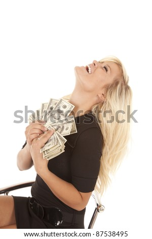 A woman holding a bunch of money leaning back in her chair laughing. - stock photo