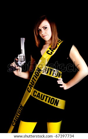 A woman holding a gun on a black background with caution tape wrapped around her.