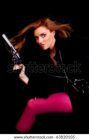 A woman holding a gun wearing pink tights, with a serious expression. - stock photo