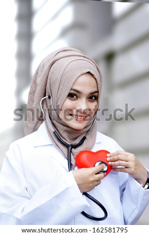 A woman holding a heart symbol                                - stock photo