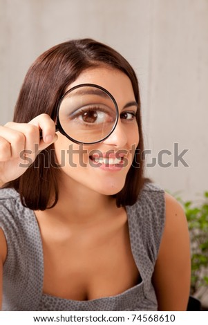 A woman holding a magnifying glass in front of her eye and looking at the camera - stock photo
