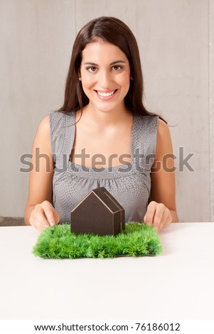 A woman holding a model house which is sitting on a turf of grass - stock photo