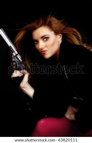 A woman holding a pistol on a black background with a serious expression on her face.