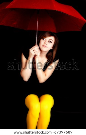 A woman holding a red umbrella and wearing yellow tights peeking out into the darkness.