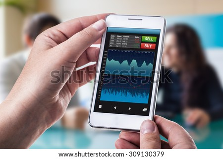 a woman holding a smart phone running a trading or forex app with charts and data - stock photo